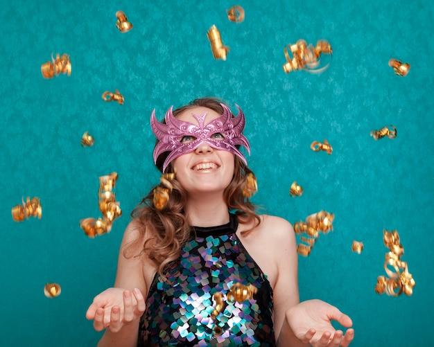 Mulher sorridente com máscara e chovendo fitas