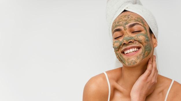 Mulher sorridente com máscara facial natural e espaço de cópia