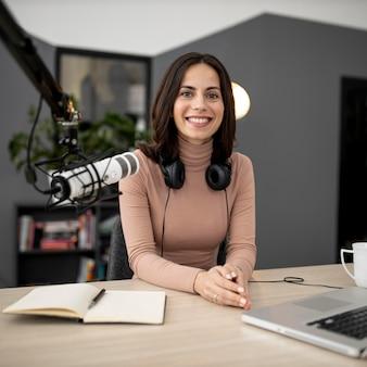 Mulher sorridente com microfone e notebook em um estúdio de rádio