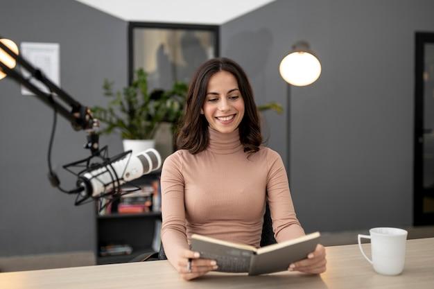 Mulher sorridente com microfone em um estúdio de rádio