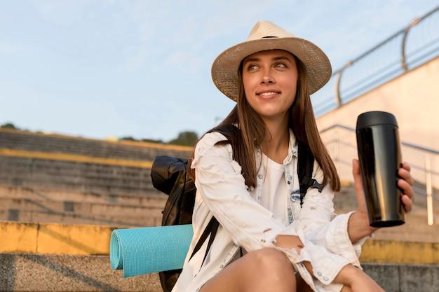 Mulher sorridente com mochila e chapéu segurando uma garrafa térmica enquanto viaja