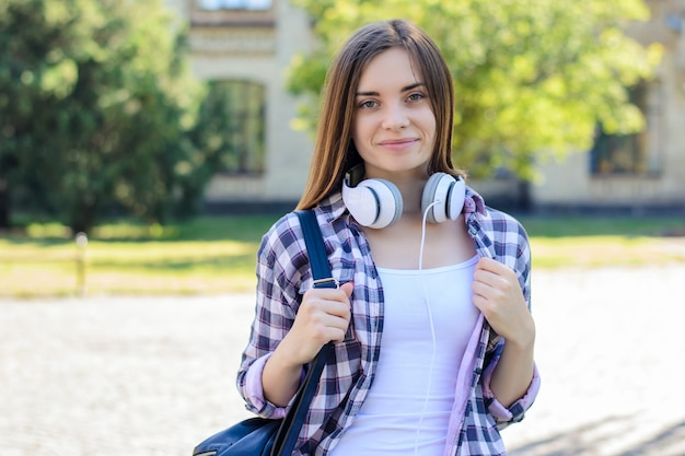 Mulher sorridente com mochila e fones de ouvido no campus