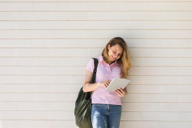 Mulher sorridente com mochila usando tablet em fundo branco