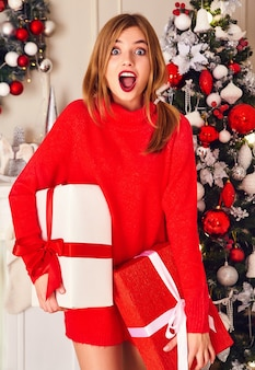 Mulher sorridente com muitas caixas de presente se passando perto da árvore de natal decorada