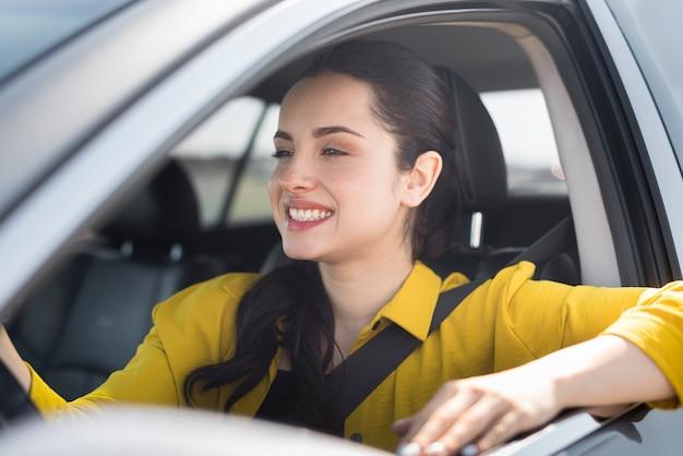 Mulher sorridente, com o cinto de segurança