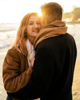 Mulher sorridente com o namorado na praia no inverno