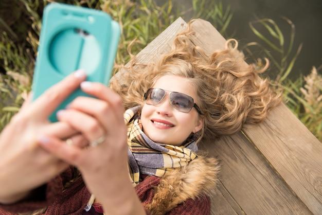 Mulher sorridente com óculos escuros deitada no cais fazendo uma selfie