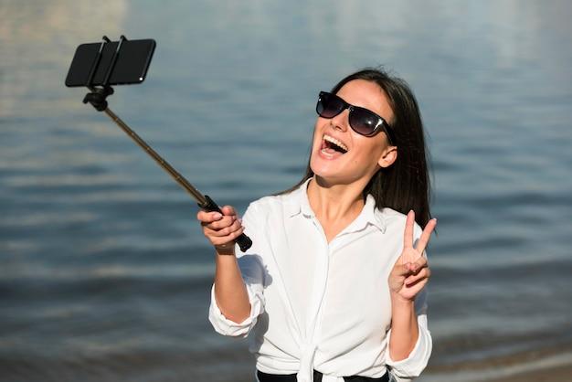 Mulher sorridente com óculos escuros tirando selfie na praia e fazendo sinal de paz