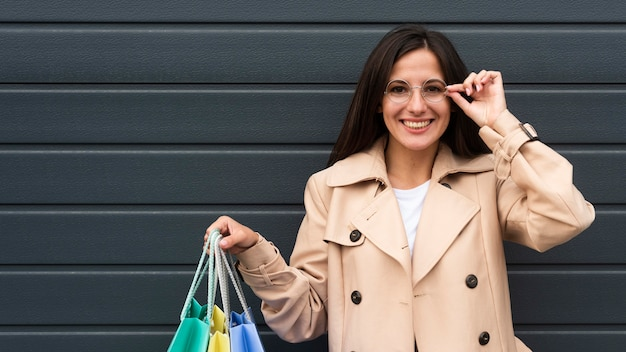 Mulher sorridente com óculos segurando sacolas de compras