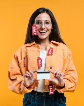 Mulher sorridente com óculos segurando um cartão de crédito enquanto é coberta por etiquetas de venda