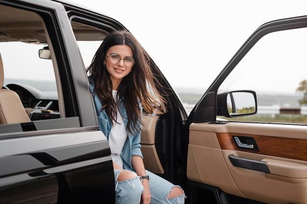 Mulher sorridente com óculos viajando sozinha de carro