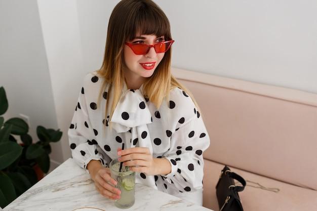 Mulher sorridente com os lábios vermelhos, segurando a bebida, sentado no sofá no café