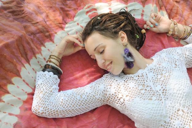 Mulher sorridente com os olhos fechados descansando ao ar livre no tapete, parque de outono