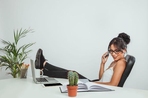 Mulher sorridente com os pés na mesa e conversando ao telefone