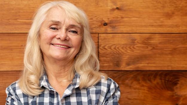 Mulher sorridente com parede de madeira como pano de fundo