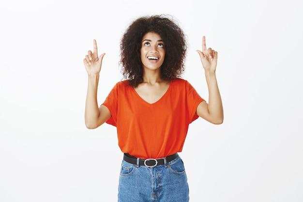 Mulher sorridente com penteado afro posando no estúdio