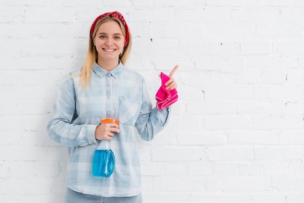 Mulher sorridente com produtos de limpeza de limpeza