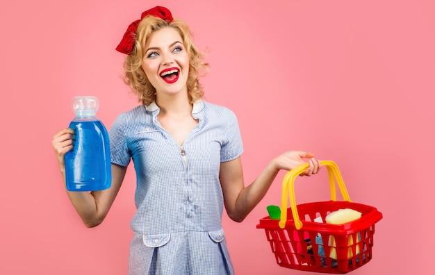 Mulher sorridente com produtos de limpeza. limpadora feminina mantém uma cesta com produtos de limpeza. tarefas domésticas.