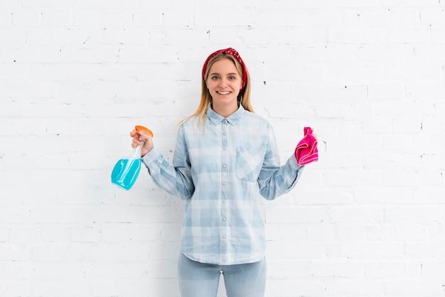 Mulher sorridente com produtos de limpeza