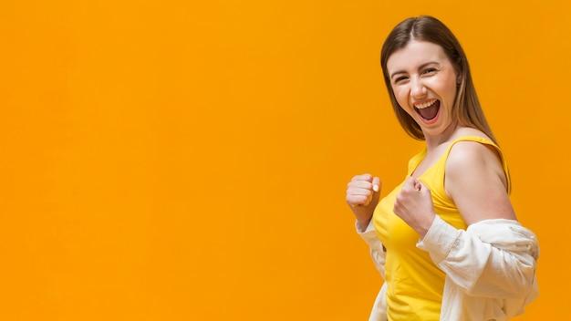 Mulher sorridente com punhos prontos para lutar