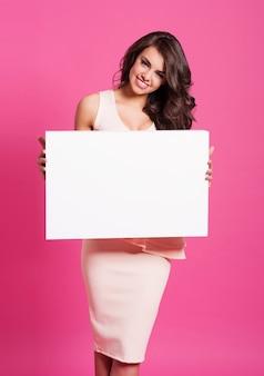 Mulher sorridente com quadro branco vazio