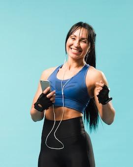Mulher sorridente com roupa de ginástica curtindo música em fones de ouvido