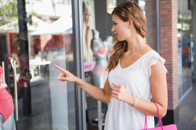 Mulher sorridente com saco de compras apontando a janela