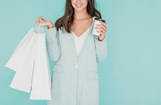 Mulher sorridente com sacolas brancas e café