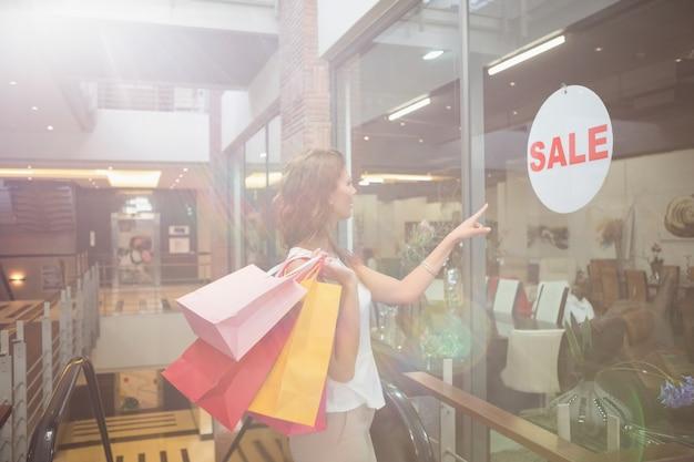 Mulher sorridente com sacolas de compras apontando a janela