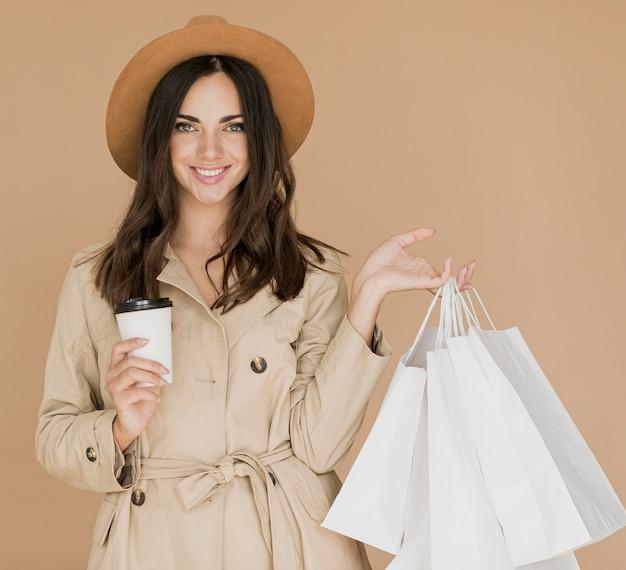 Mulher sorridente com sacolas de compras e café