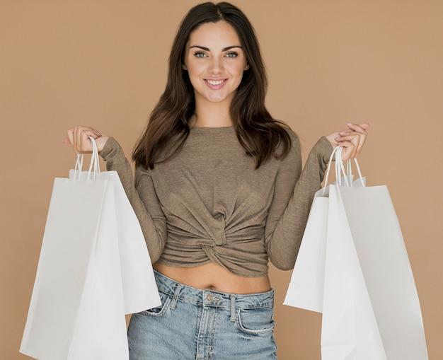 Mulher sorridente com sacolas de compras em ambas as mãos