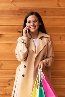 Mulher sorridente com sacolas de compras falando ao telefone