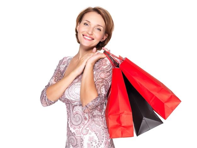 Mulher sorridente com sacolas de compras na parede branca