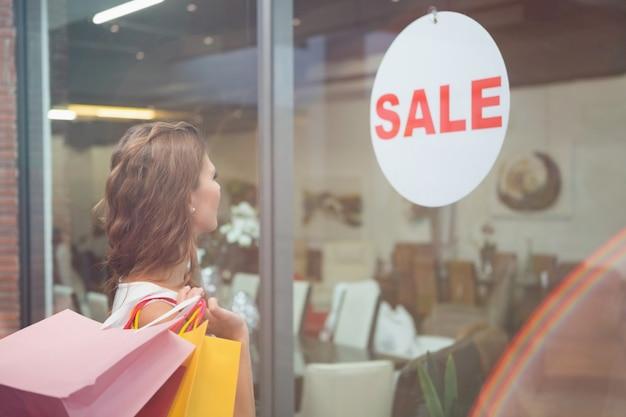 Mulher sorridente com sacolas de compras olhando a janela