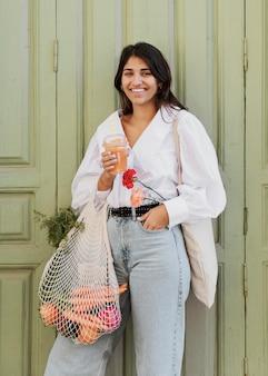 Mulher sorridente com sacolas de compras tomando suco ao ar livre