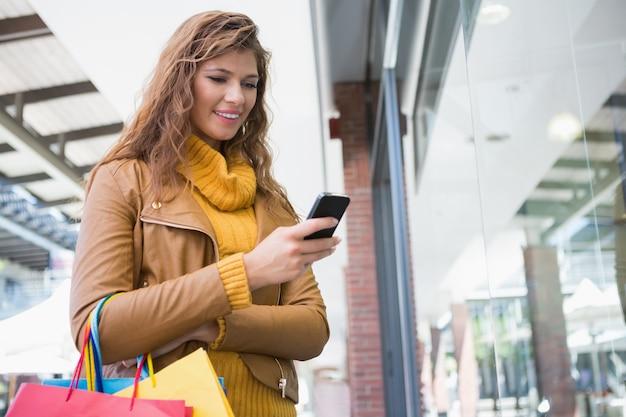 Mulher sorridente com sacolas de compras usando smartphone