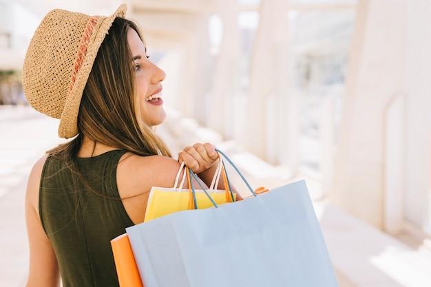 Mulher sorridente com sacolas de compras