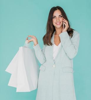 Mulher sorridente com sacos de compras, falando ao telefone