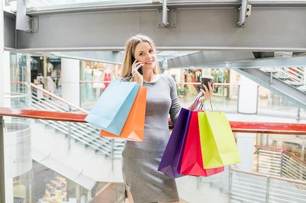 Mulher sorridente com sacos de compras, falando no celular no shopping
