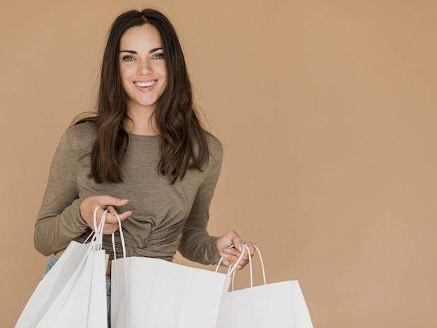 Mulher sorridente com sacos de compras, olhando para a câmera