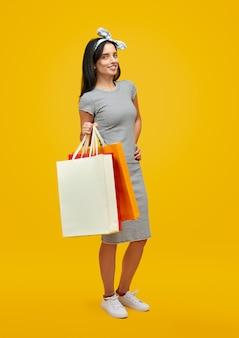 Mulher sorridente com sacos de papel