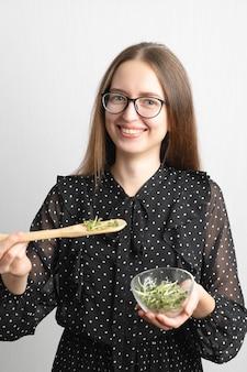 Mulher sorridente com salada de microgreens