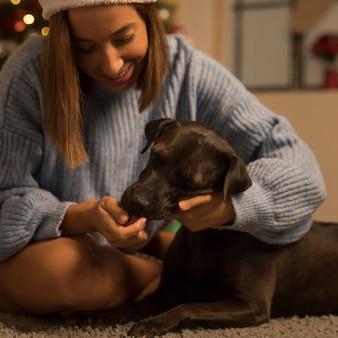 Mulher sorridente com seu cachorro no natal