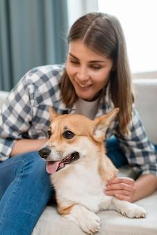Mulher sorridente com seu cachorro no sofá
