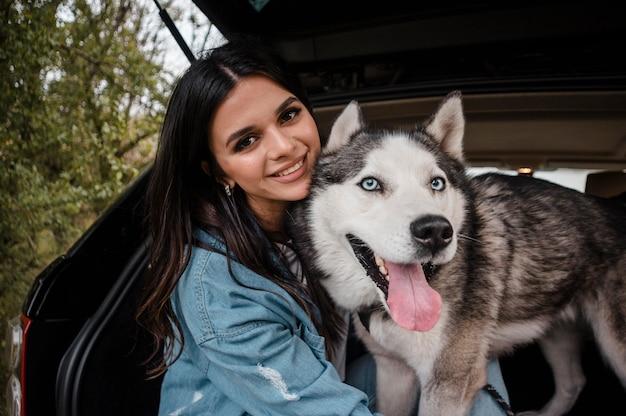 Mulher sorridente com seu husky fofo viajando de carro