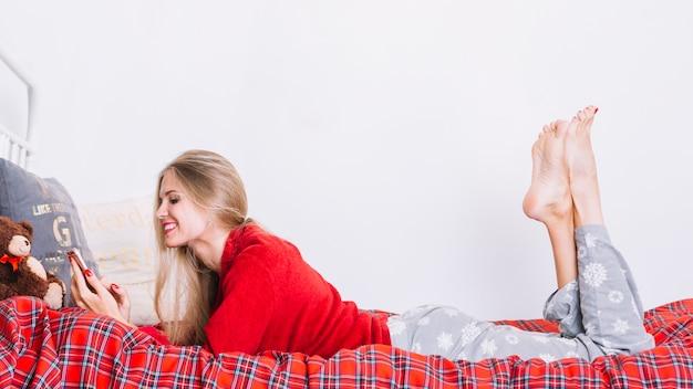 Mulher sorridente, com, smartphone, mentindo cama