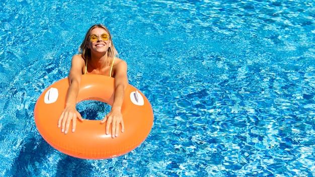 Mulher sorridente com tábua de salvação na piscina