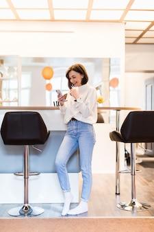 Mulher sorridente com telefone em pé na cozinha panorâmica com paredes brilhantes mesa alta e cadeiras de bar