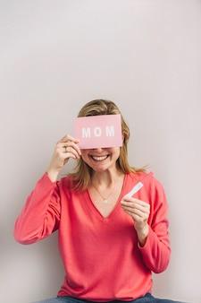Mulher sorridente, com, teste gravidez, e, cartão