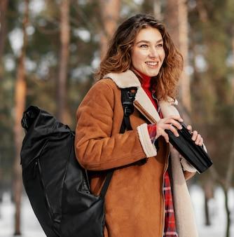 Mulher sorridente com tiro médio carregando mochila